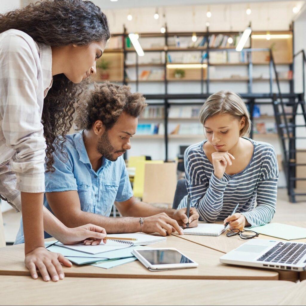 Deux personnes assises suivant une formation en management de projet en entreprise accompagné par le formateur se penchant au dessus d'eux.