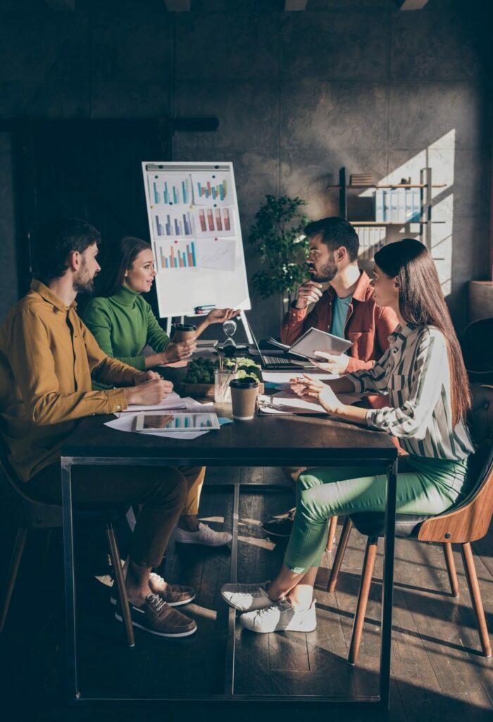 Quatre salarié d'entreprise autour d'une table de réunion devant un paperboard se formant au Management de Projet